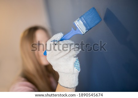 Decorator painter hand painting blue color wall with roller. Stok fotoğraf ©