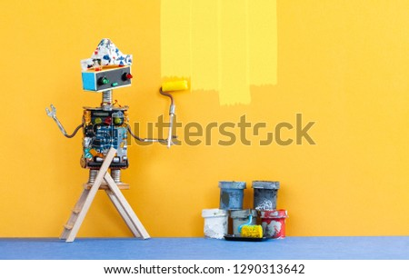 Decorator robot repaints the wall of the room in yellow color. Funny painter robot toy and indoors interior redecoration concept. copy space.