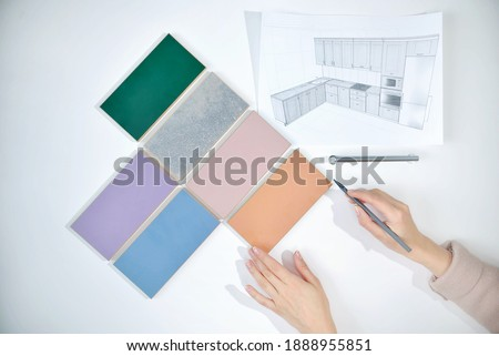 decorator's hands Choosing samples of materials and colors of woods for interior project. Top view. kitchen countertop material texture from samples. decors boards on the furniture industry