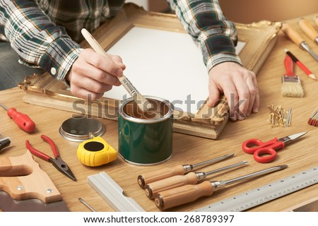 Decorator varnishing a wooden frame hands close up with DIY tools, hobby and craft concept
