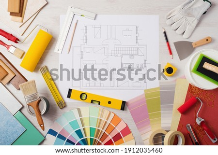 Decorator work table with house project, paint brush and painting roller, color swatches and tools, top view Stok fotoğraf ©