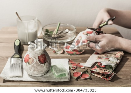 Decoupage accessories on a table - brush, scissors, paper, tissues, sponge, pencils, paint. Hands cutting flowers in the background.