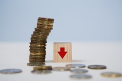 Decrease in income. Global financial crisis. Bankruptcy, lack of money. Stack of coins, wooden cube, arrow to down sign