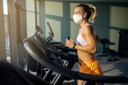 Dedicated female athlete jogging on running track while wearing protective face mask in a gym during coronavirus epidemic.