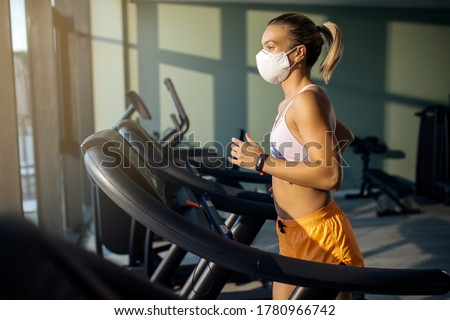 Dedicated female athlete jogging on running track while wearing protective face mask in a gym during coronavirus epidemic.  Stockfoto ©