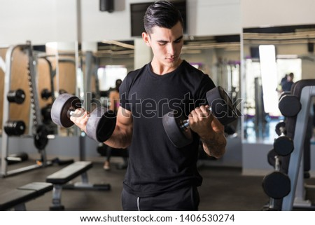 Dedicated male athlete showing devotion towards his body in health club