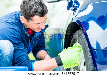 Dedicated male worker using microfiber car wash mitt for cleaning rim outdoors