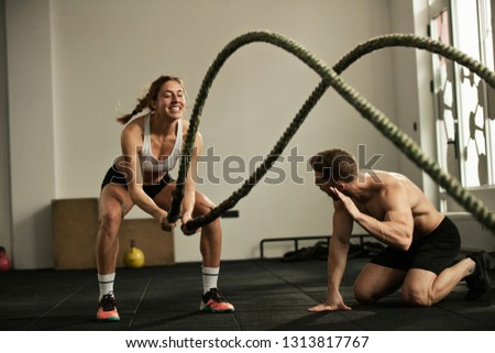 Dedicated sportswoman exercising with battle rope while coach is encouraging her during cross training in health club.