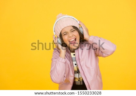 Dedicated to singing. Small singer yellow background. Happy girl enjoy singing to music. Singing lesson. Vocal exercises. Learn to sing. Music school. Her singing voice is really lovely.