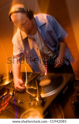 Deejay mixing vinyl records on a turntable players in blured motion