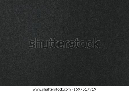 Deep black color of a blank sheet of paper with gradient. Gloomy background for text and design.