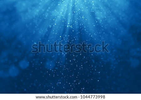 deep blue ocean waves from underwater background with particles flowing movement, light rays shining through
