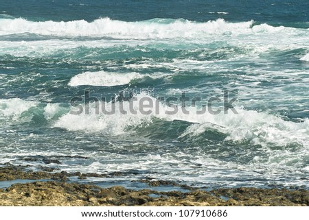 Deep blue ocean waves white with foam roll on rocky shore.