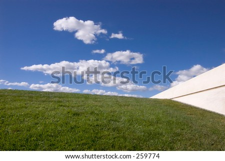 Deep blue sky, fluffy white clouds and green grass, wall, all joining at a point.