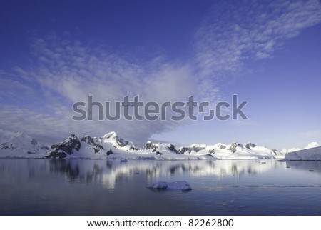 Deep blue sky, snow capped mountains and iceberg in foreground with calm waters. Taken at Paradise Harbor, Antarctica. With Copy Space (above).