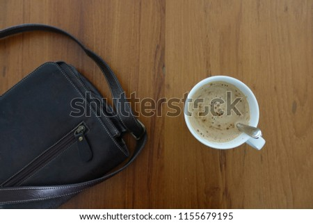 deep brown leather bag with cup of coffee on wooden table #1155679195