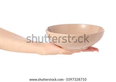 Deep brown soup plate in hand on white background isolation #1097328710