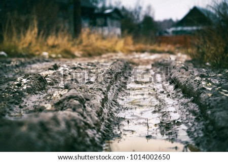 Deep car rut on russian dirt road in winter thaw                               #1014002650