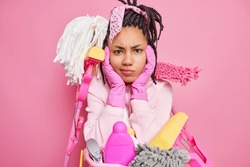 Deep cleaning and cleanliness concept. Dissatisfied sullen dark skinned woman keeps hands on face has unhappy expression as has to do housework surrounded by cleaning supplies poses indoor alone