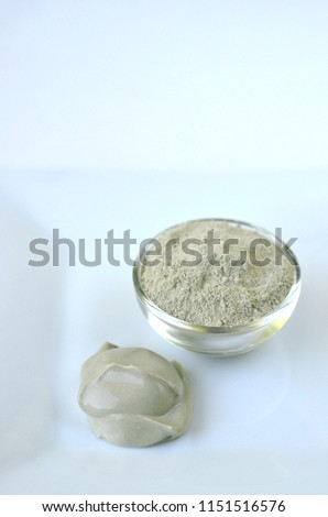 Deep cleansing cosmetic bentonite (montmorillonite) clay for beauty spa face mask, body detox and hair treatments. Clay powder and mask in glass bowl.