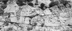 Deep damages of high shore, gaps split, cavity, groove track on a big sharp stones. Debris, scratch marks of cut ruined blocks rock. Gray dirt bump map of old grunge steep cliff for 3d volume backdrop