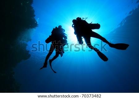 Deep Explorer Technical Divers silhouetted against sunburst