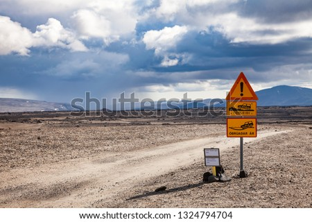 Deep ford and rough gravel road warning roadsign and Road F26 closed due to snow alert sign at Ódáðahraun lava field in Highlands of Iceland, Scandinavia. Rainy cloud is seen in background