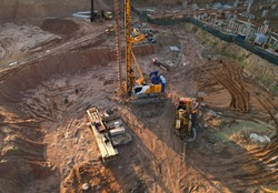 Deep foundation machine. Drilling rig and Pile driver at construction site. Pile driven into ground by vibrating hydraulic hammer. Foundations construction work. Ground drilling and Piling Contractor.