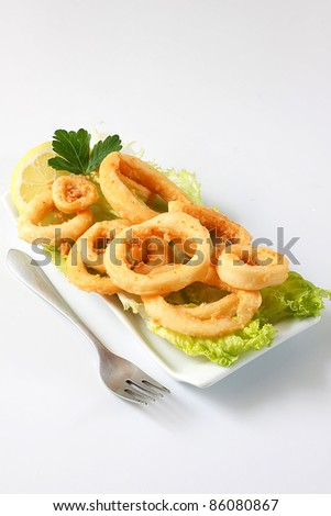 deep fried calamari with lettuce and lemon - stock photo