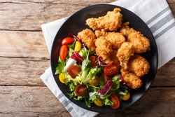 deep-fried chicken wings in breadcrumbs and fresh vegetable close-up on a plate. horizontal top view from above