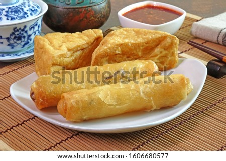 Deep fried crispy Spring rolls and fried Tofu, served with sweet and spicy chili sauce. Vegetarian food for Vegetarian festival. Selective focus