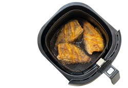 Deep fried fish in tray of hot air fryer or oil-free fryer, top view image, isolated on white background. The concept for modern and healthy cooking. The fried fish is Snakeskin gourami fish.
