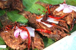 Deep fried fish with chili and onions on banana leaves. Thai street food
