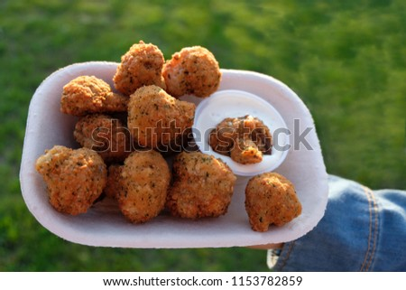Deep fried mushrooms in batter with parsley and seasoning being held in a generic take out container. Mayo sauce with dill herb dip is on the side, slightly dripping. Side View.