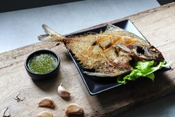 Deep fried promfet or snapper fish with fish sauce in the black plate on the wooden table