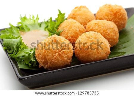 Deep Fried Rice Balls with Salmon and Cream Cheese. Garnished on Green Leaf with Nuts Sauce