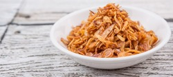 Deep fried shallots for garnishing in white bowl over wooden background