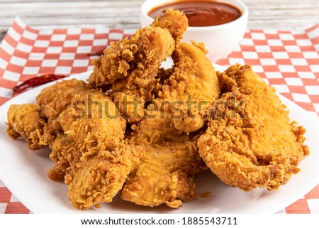 deep fried southern style breaded chicken tenders or chicken fingers on a white plate with dipping sauce Stock photo ©