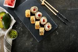 Deep Fried Sushi Rolls with Salmon and Philadelphia Cream Cheese Top View. Hot Crispy Tempura Maki Set with Tuna Fish and Nori Seaweed on Natural Black Stone Slate Background with Copyspace