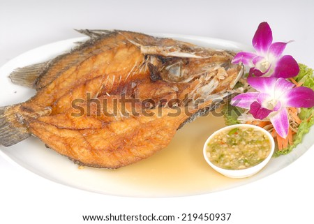 Deep Fried Tilapia fish fried with sauce spicy appetizing food on white plate in studio,Fish dish - deep fried fish with vegetables on white dish