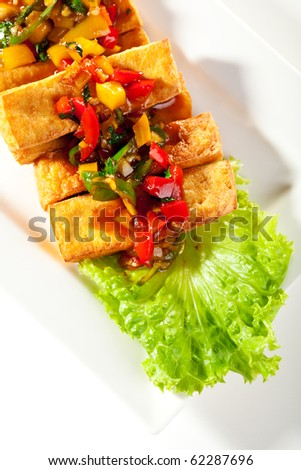 Deep Fried Tofu Topped with Fried Vegetables. Garnished with Sauce and Fresh Salad Leaf