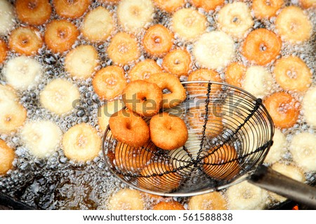 Deep frying medu vada in the pan. Medu Vada is a savoury snack from South India, very common street food in the India.