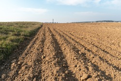 Deep furrows in the ground after working the tractor with the plow. Plowing the land. treatment of the top layer of soil to saturate the soil with oxygen and destroy the seeds and roots of weeds.