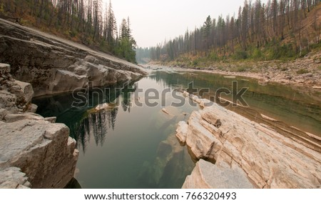 Deep Green Pool of still water in Meadow Creek Gorge in the Bob Marshall Wilderness area during the 2017 fall forest fires in Montana United States #766320493