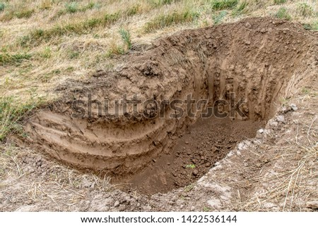 Deep hole in the ground dug by an excavator Stock fotó ©