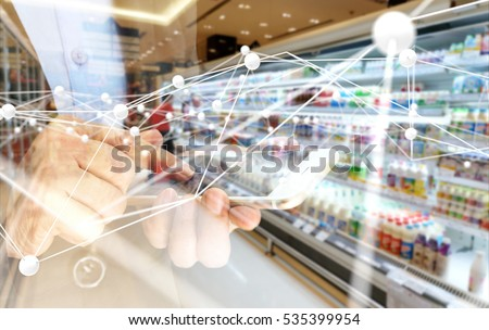 Deep learning , Neural networks , Machine learning and artificial intelligence concept. Atom connect with hand holding mobile phone and blur retail shop store background