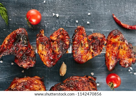 Deep Roasted Hot, Spicy Buffalo Style Chicken Wings on a Skewer Top View. Macro Photo of Appetizing Barbecue Poultry Wing with Spices, Tomatoes, Garlic, Salt on Black Blur Background
