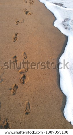 deep sea deep breath and kid's footprints on the sand #1389053108