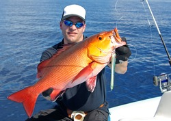 Deep sea fishing, man holding a red snapper fish.