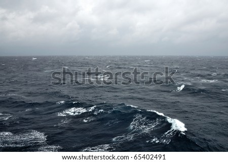 Deep sea water waves and stormy sky. - stock photo
